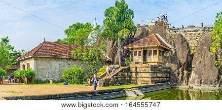 ANURADHAPURA SRI LANKA - NOVEMBER 26 2016: The complex of Isurumuniya Viharaya with the view on the Rock Temple pond and the Stupa hidden behind the trees on November 26 in Anuradhapura.