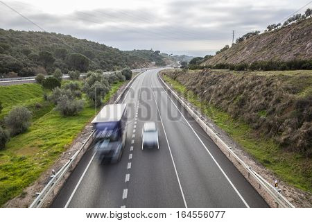 Car overtaking to truck that moves by slow vehicles lane. Cerro Muriano Cordoba