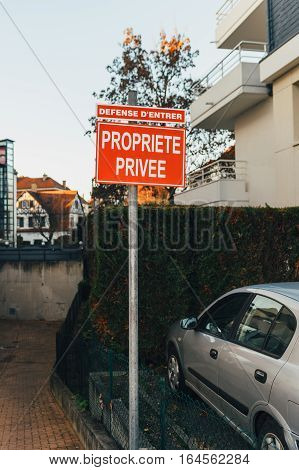 Propriete Privee - Private Property translated from French - with house garden and parked car in French city