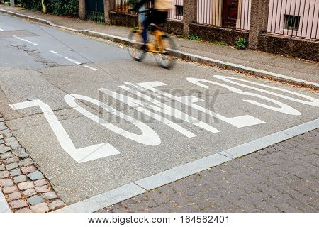 Traffic sign on asphalt speed limit of 30 kilometers per hour with cyclist silhouette on his bike