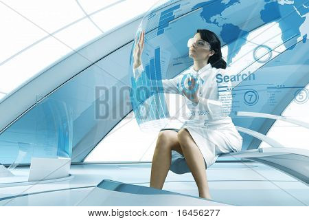 Sexy brunette operating transparent future touch interface. Sits in the air chair. Impressive specially designed for this series abstract bio interior. Interfaces collection.