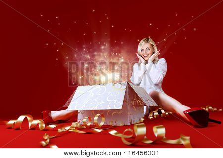 Magic surprise for a pretty blonde! Charming girl in white dress spread shot. Gift box in center. Light beams and stars coming from the box. Red background. Amazing face expression. Sense of holiday.
