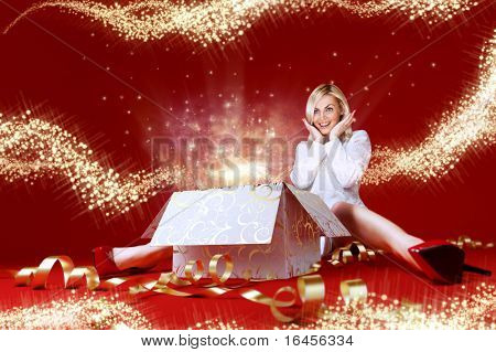 Majestic gift for a pretty blonde! Sense of holiday. Charming girl in white dress spread shot. Gift box in center. Light beams and stars coming from the box. Red background. Amazing face expression.