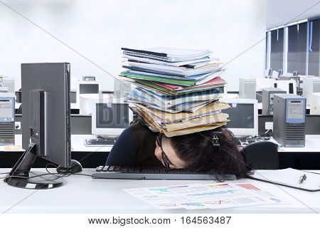 Picture of young entrepreneur sleeping on the desk with stack of documents over her head