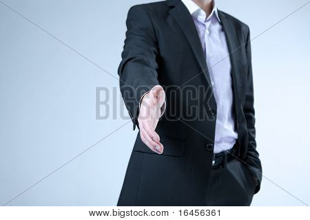 Businessman stretches out hand for handshake. Hello | welcome | offer | contract | agreement etc. classic business concept. No head, no face on the shot.