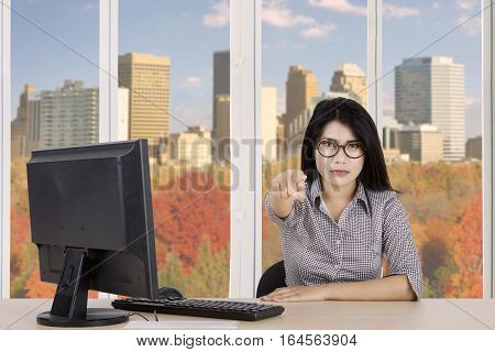 Young Asian businesswoman looks angry while pointing finger at you with computer on the table shot in the office