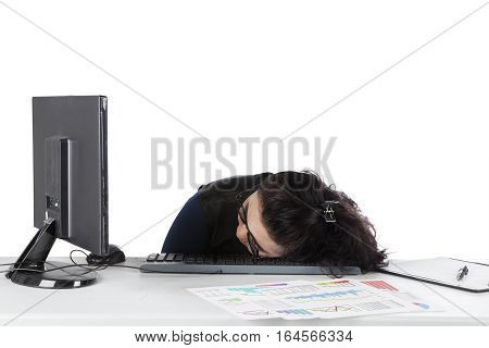 Young businesswoman sleeping on the desk in front of her computer isolated on white background