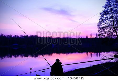 Silhouette of fisherman at sunset
