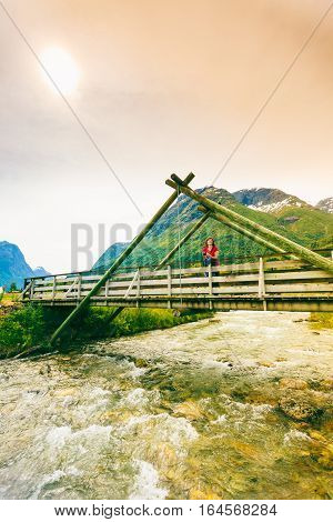 Tourism vacation and travel. Woman tourist relaxing on bridge looking at mountains landscape in norwegian village Oppstryn Sogn og Fjordane county. Norway Scandinavia.