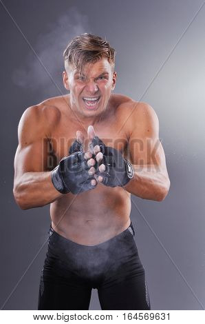 Muscular Fighter Claps With Dusty Gloves For Fight And Motivate Himself. Boxing On Gray Background.