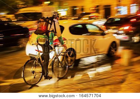 Bicycle Messenger In City Traffic At Night