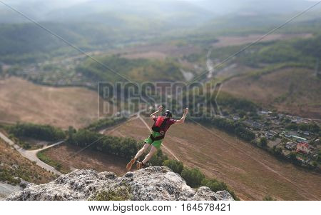 man jumps from the cliff in mountains, crimea