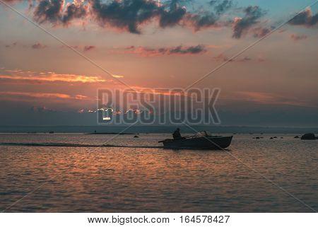 fisherman on boat, sunrise motorboat nice clouds