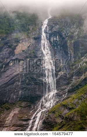 Norway Geiranger fjord. On the banks are located cliffs up to 1400 meters with flowing waterfalls and glaciers. Foggy morning.