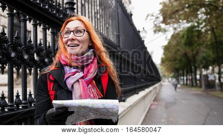 Yong woman tourist with red hair and glasses looking map in Vienna near Neue Burg, Austria, close up