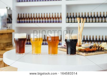View on variety of craft beer in glasses and snack board on table