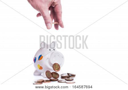 Man hand insert coin into piggy bank isolated on white