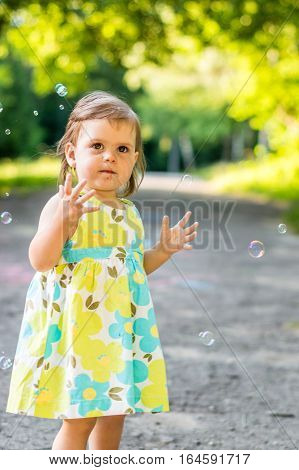little girl catches bubbles in the Park