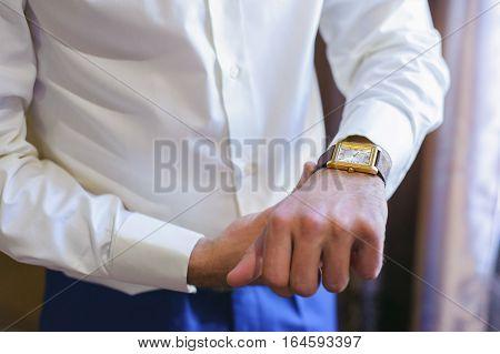 A Man In A White Shirt Straightens His Cufflinks