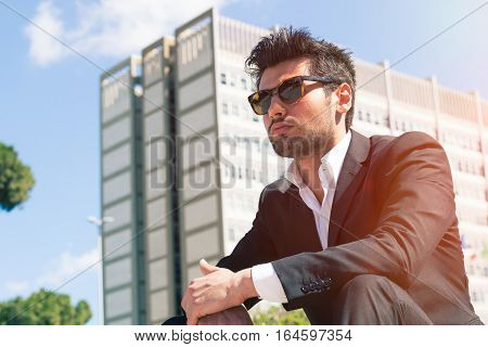 Young handsome man with sunglasses. Career and job opportunities in the city. Sitting watching. Behind him a building with offices.