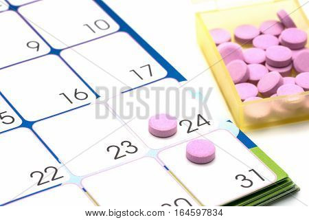 Medical pills capsule in pill box with calendar on white background.