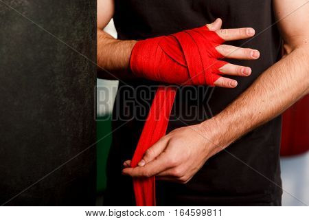 Man wears red boxing bandages on his hands