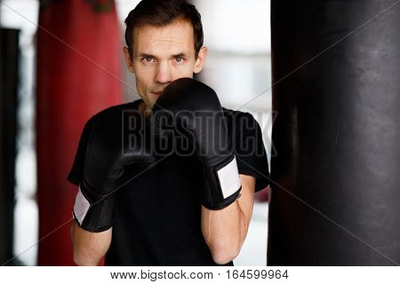 Portrait of young sportsman with gloves in gym
