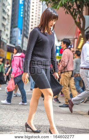Hong Kong, China - December 6, 2016: An elegant Asian woman with high heels walking between Hennessy Road and Yee Wo Street, a busy downtown junction with fashion and luxury store in Causaway Bay.