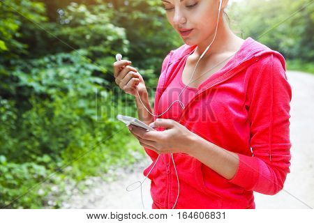 Young lady runner on a rural road in the morning with phone