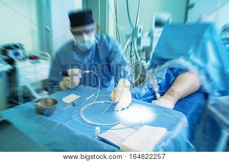 doctor during the surgery preparing instrument for procedure