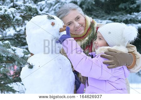 grandmother and granddaughter have fun outdoors in winter