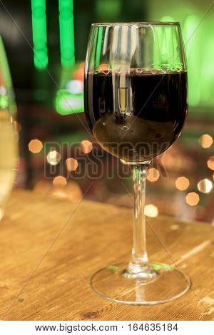 A glass of red wine on a blurred background of lights, with a glass of white wine reflected in it. Selective focus