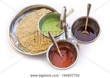 Indian bread served with the traditional assortment of sauces, in the typical tableware, on a white background