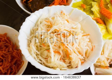 Sauerkraut and other pickled vegetables in white bowls