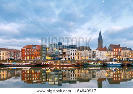 View of the embankment and houses along the river at sunset. Gent. Belgium.