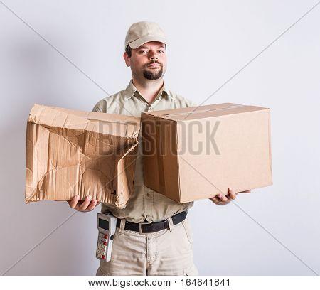 Messenger in uniform holding normal and broken parcels, white background