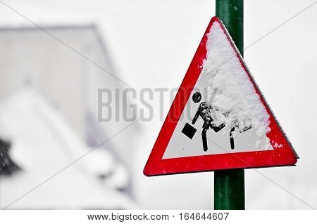 School zone crossing road sign covered with snow in winter