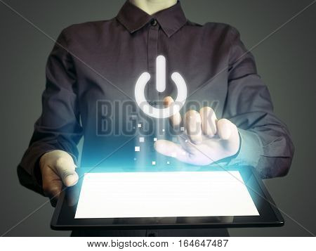 Image of a person with tablet in her hands. Finger touches the power button icon. ON- OFF concept of something