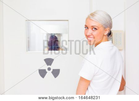 a dental assistant is taking an x-ray image of a patient's teeth