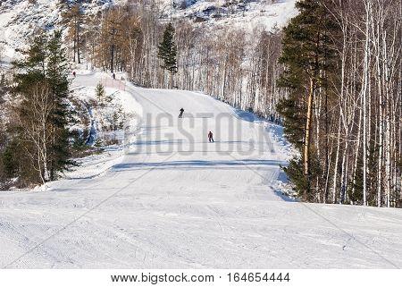 Mountain skiers climb down a mountain on the route