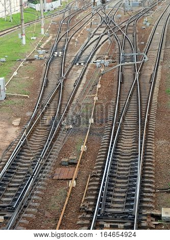 Industrial landscape with railroad tracks on concrete railway sleepers, arrows and track equipment vertical top view