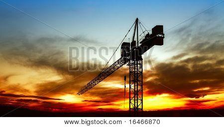 La grúa de la construcción en puesta de sol