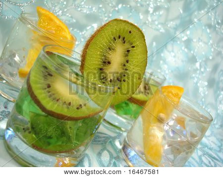 Glass of water with kiwi and lemon over blue background