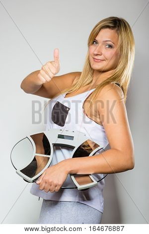 Diet fitness slimming loosing weight concept. Happy blonde woman holding weighing machine showing thumb up gesture.