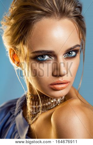 Beautiful fashion woman with brown hair and evening makeup wearing blue purple party outfit. Jewelry and Beauty. studio shot.