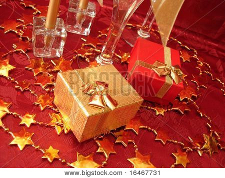 golden and red gift boxes, stars on beautiful background with champagne glasses