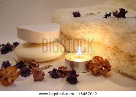 Spa essentials (soap, candle and towel with flowers)