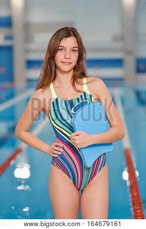 Girl learning to swim with board in the swimming pool.