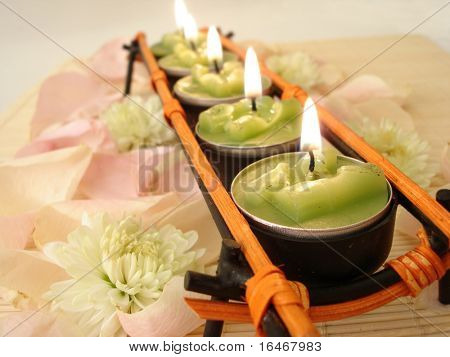 row of green candles over  straw matt with rose petals