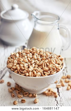 Puffed wheat cereal in white bowl with pitcher of milk in background